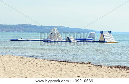 Blue water slide on sea beach kids game and jump area close up outdoor.