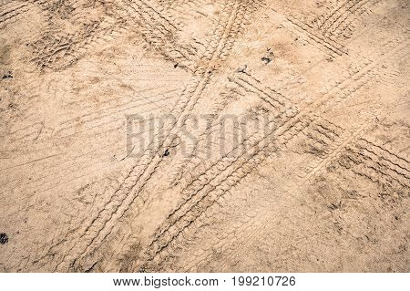 Tire tracks on dirt road urban non asphalt traffic way with tire tracks of many type of vehicles and foot prints.