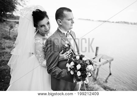 Stunning Wedding Couple With A Bouquet Hugging On The Lakeside. Black And White Photo.