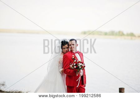 Stunning Wedding Couple With A Bouquet Hugging On The Lakeside.
