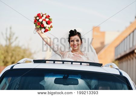 Portrait Of A Flawless Bride Looking Out Of The Sunroof In The Wedding Car.