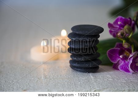 Spa treatments on wooden table. Sea salt spa stones orchid and burning candles.