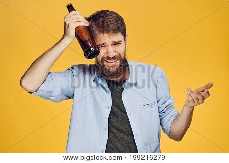Man with a beard holding a bottle of beer on a yellow background, alcohol, emotions.