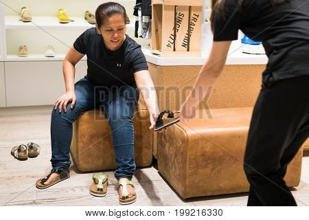 Mega Bangna Shopping Center, Bangkok, Thailand - August 5, 2017: Middle-aged woman sitting and buying shoes in the shop. She choose the healthy shoes for the elderly. Because she have problems with her knee