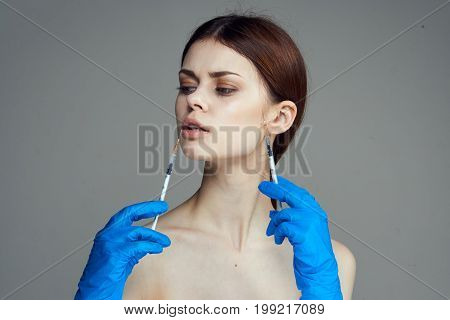 Young beautiful woman holds syringes in rubber gloves on gray background.portrait, plastic surgery.