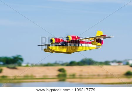 Radio controlled model hydroplane flying on a nice cloudy day over Guadiana River in Badajoz Extremadura Spain