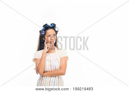 'young Thoughtful Housewife With Curlers, Wearing Apron, Isolated On White