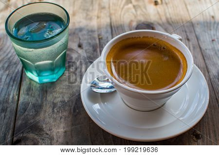 Strong And Dark Coffee In A White Porcelain Cup Served With A Glass Of Water On A Side On A Wooden T