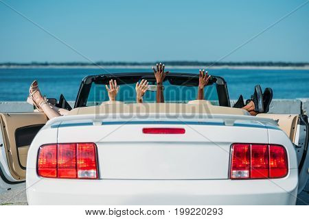 partial view of women resting in car at seaside together
