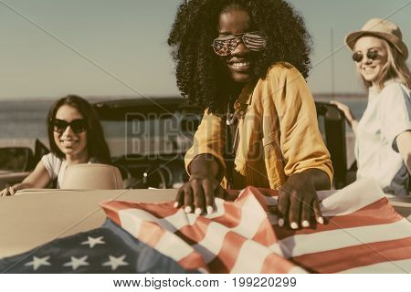 Multiethnic Young Women Resting In Car With American Flag At Seaside