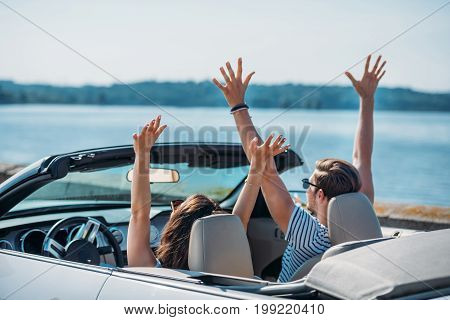Young Couple With Outstretched Arms Sitting In Car Together