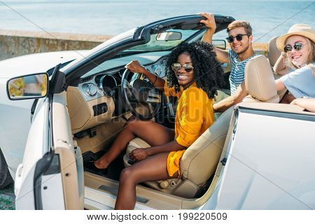 multicultural young happy friends riding car together at seaside