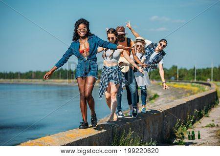 Multicultural Young Friends Walking On Parapet Together At Seaside