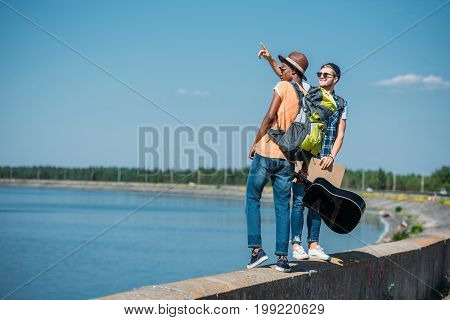 Multicultural Men With Empty Cardboard Walking On Parapet While Hitchhiking Together