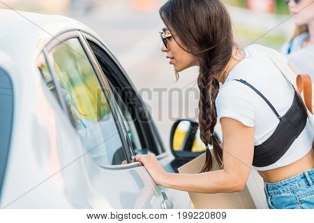 side view of asian woman talking with driver while hitchhiking with friends