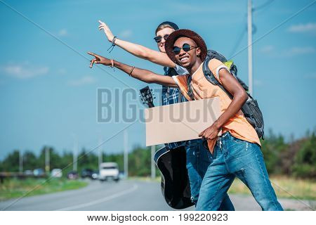 Multiethnic Men With Empty Cardboard Waving To Stop Car While Hitchhiking During Trip