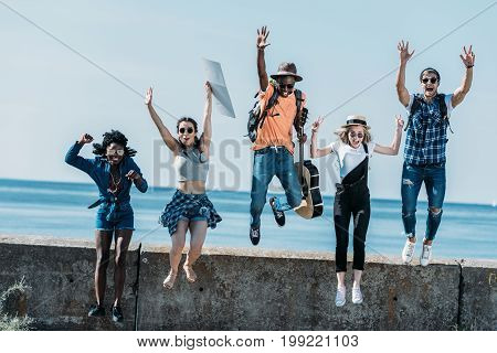 Multicultural Group Of Young Friends Jumping Of Parapet Together