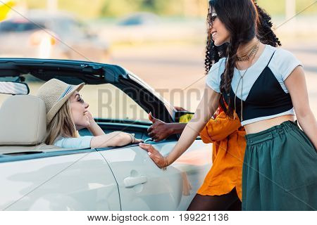 Side View Of Multiethnic Smiling Women Having Conversation Near Car