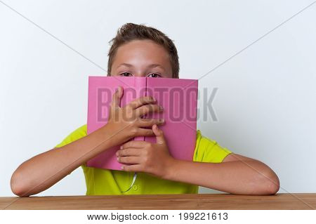 12 years old boy sitting at the table and covering his face with the book. Education concept.