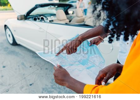 Partial View Of African American Man Pointing At Map While Choosing Destination With Girlfriend