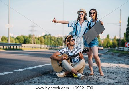 Multicultural Friends With Empty Cardboard Hitchhiking While Traveling Together