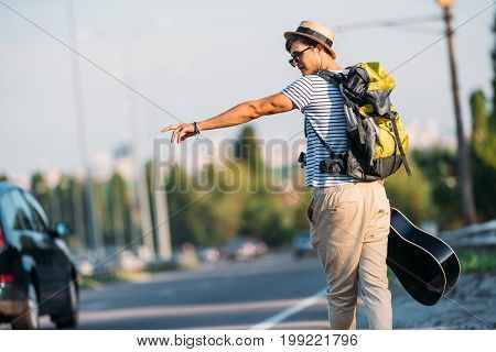 Back View Of Young Man With Guitar Gesturing To Stop Car While Hitchhiking Alone