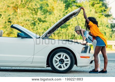 Side View Of Multiethnic Women Standing Near Broken Car During Trip