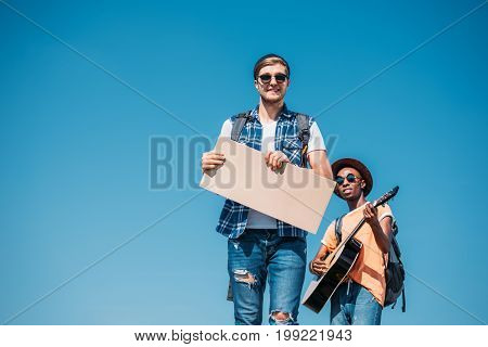 Portrait Of Multiethnic Men With Empty Cardboard Hitchhiking Together Against Blue Sky
