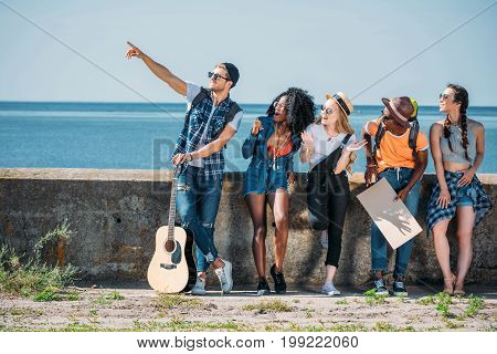 multiethnic young friends with guitar and empty cardboard pointing away while hitchhiking together
