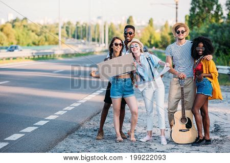 Multicultural Group Of Young Hitchhikers With Map And Empty Cardboard Standing At Sidewalk Of Road