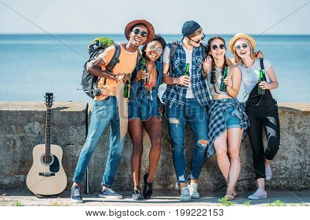 multiethnic happy friends with bottles in hands standing at parapet together