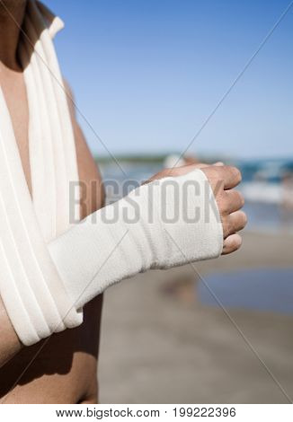 closeup of a young caucasian man on the beach with a sling and a bandage in his wrist