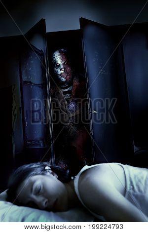 scary horror killer clown and sleeping woman