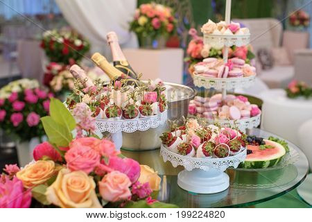 Strawberry in chocolate on the table with sweets and champagne around everything is decorated with flowers with roses. Stand with pink sweet macaroons and bottles on champagne on background.
