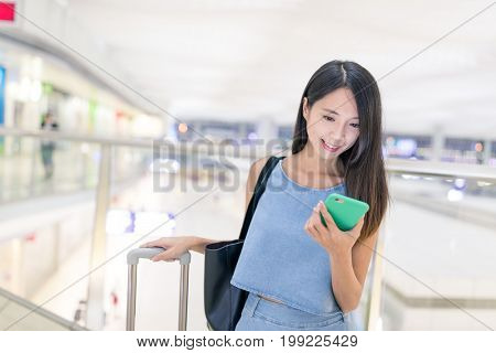 Woman travel in airport with her cellphone