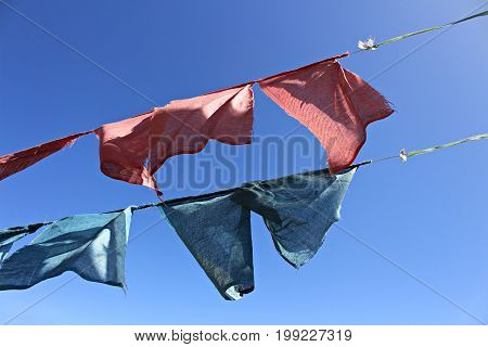 Old pale mantra flags from Bhutan and bright blue sky
