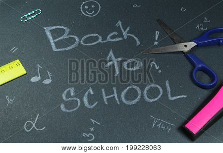 Sign ,,Back to school` on black background/This is notice ,,Back to school` on black background with school aids.