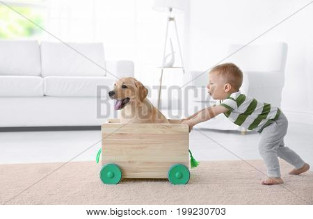 Cute child and Labrador Retriever playing with wooden toy cart at home