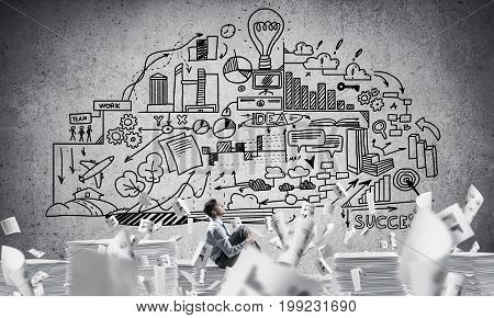 Businessman looking away while sitting on pile of documents among flying papers with business-plan information on background. Mixed media.
