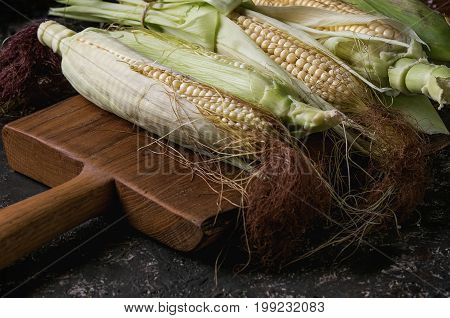 Young raw uncooked corn cobs in leaves on wooden chopping cutting board. Close up over dark brown concrete texture background.
