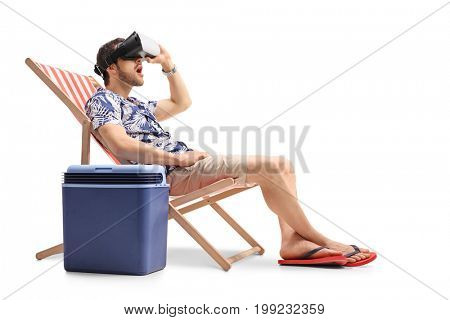 Tourist with a VR headset sitting in a deck chair next to a cooling box isolated on white background