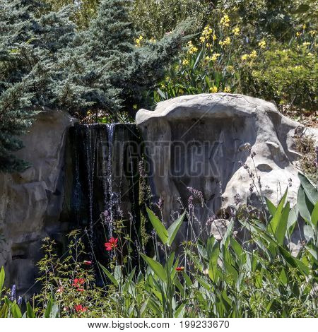 A small artificial waterfall between large stones, surrounded by greenery and flowers