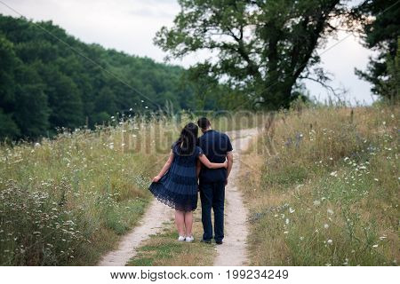 Couple In Love Embracing And Walking On Footpath Outdoors Near The Forest, Back View. Free Space
