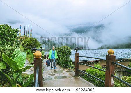 Caucasian Man Passing Through The Passage With Foggy Trongsa Dzong View, Bumthang, Bhutan, Asia.