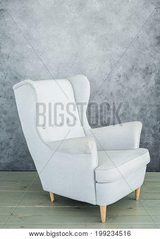 One soft gray velvet armchair near gray wall