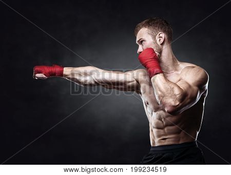 Muscular kickbox or muay thai fighter punching. Isolated, clipping path included.