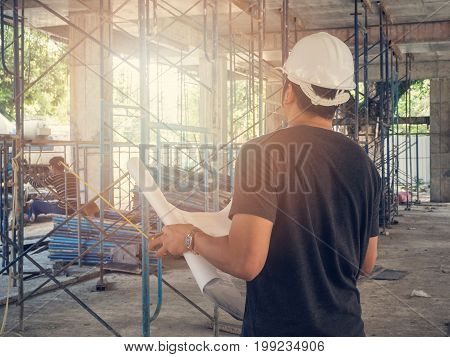 Foreman or engineer with blueprint on construction site