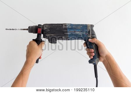 Man hands hold electric drill on white wall