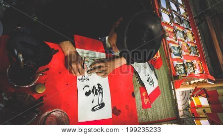 HO CHI MINH / VIETNAM, AUGUST 2017 - Scribe skilled in calligraphy of Vietnamese characters, he is writing prayer calligraphy for children