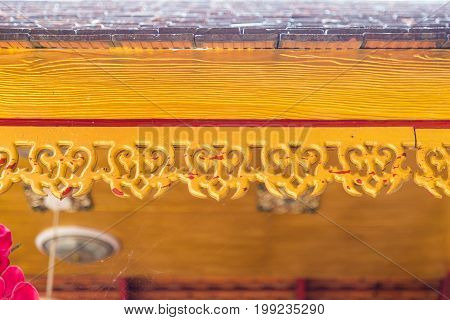 Retro wooden cornice decorate on eaves in Buddhist temple Thailand.